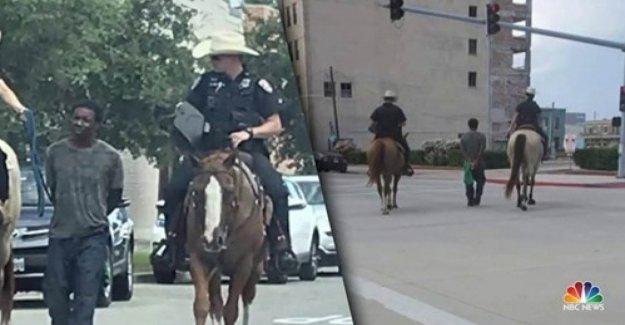 Estados unidos, africano-americano detenido y arrastrado por dos agentes de policía a caballo. La policía se disculpó