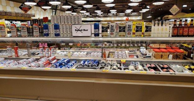 Tienda de comestibles rellenos de ensalada de la barra con el alcohol, los dulces durante la pandemia de restricciones