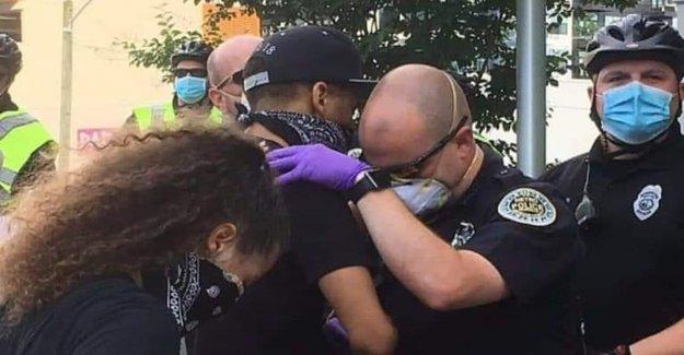 Oficial de policía ora con manifestante de 'tocar' la foto