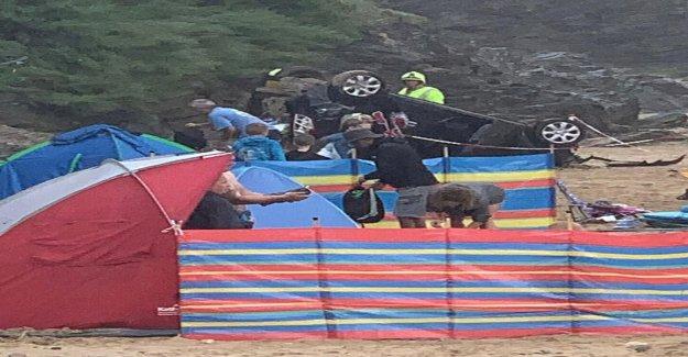 Conductor sobrevive de inmersión fuera de acantilado en la playa llena de gente
