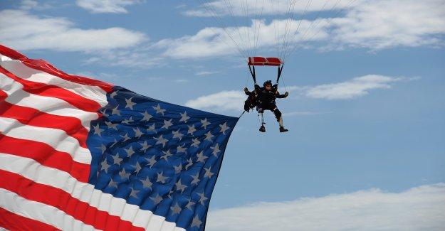 Doble amputado veterano saltos por encima de rally de Sturgis con el gigante bandera de los estados unidos, Trump 2020 paracaídas