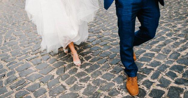 La novia y el novio pausa fotos de la boda para ayudar al hombre golpeado por el coche