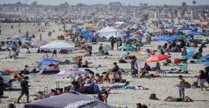 Miles acuden a las playas para vacaciones de fin de semana como COVID tasa se eleva, pero la tasa de mortalidad se mantiene estable